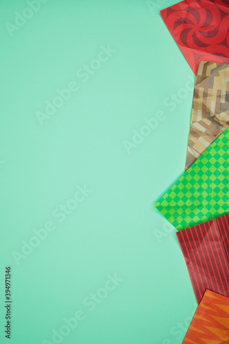 Foto Mix of colored wrapping paper on a green background.