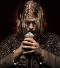 Portrait Of Serious Viking Holding Sword Against Colored Background