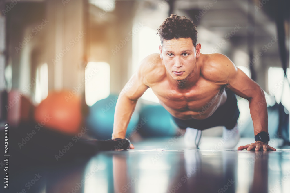 Fototapeta Young male push up exercise to build up chest muscle strength at fitness sport club.