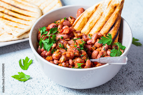 Cuadros en Lienzo Stewed beans in tomato sauce with herbs and grilled tortillas