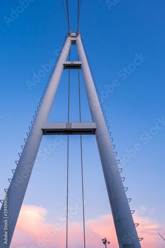 Fototapeta premium 晴れた夕焼け空に高くそびえ立つ、つり橋の鉄塔