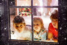 Three Cute Children Sitting By Window On Christmas Eve. Two School Kid Boys And Toddler Girl, Siblings Looking Outdoor And Dreaming. Family Happiness On Traditional Holiday