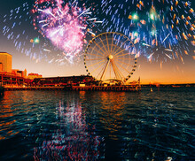 Cityscape With Ferris Wheel  Illuminated At Sunset With Fireworks Over Sky Near Waterfront. Seattle, Washington, USA