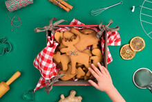 Top View Of Childs Hand Reaching Freshly Backed Christmas Gingerbread Cookie Deer Form Over Green Background With Biscuits On Red Plaid Napkin Ginger, Cinnamon,dry Orange Slice And Kitchenware.