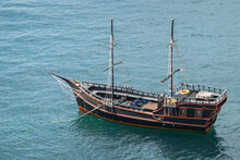 A Tourist Ship, Stylized As An Antique, Is Anchored In The Middle Of The Sea. There Are No Passengers On The Ship.