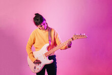 Woman Playing Guitar Against Pink Background