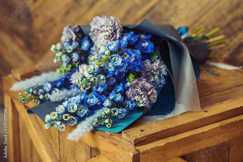Foto Blue bouquet on a wooden cover in a gray package