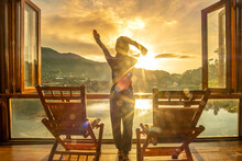 Happy Young Woman Watching Lake View At Coffee Shop In The Morning Sunrise, Ban Rak Thai Village, Mae Hong Son Province, Thailand. Travel Concept