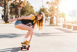 Skater girl riding a long board skate. Cool female urban sports. California style outfit. Woman on skateboard wearing pink glasses