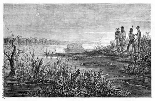 Foto Body in water of dangerous swamp full of crocodiles and other men looking at him on shore