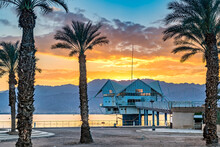 Colorful Sunrise Above Mountains And Public Beach With Promenade And Decorative Palms As Foreground, Red Sea, Middle East