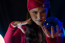 Female Fortune Teller With Crystal Ball At Home