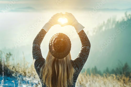 Fotografie, Obraz Happy traveler woman tourist stay on mountain top and making of love heart by hands in sunny frozen winter day