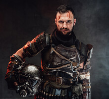 Cheerful And Smiley Post Apocalyptic Fighter Dressed In Ragged And Dirty Armour Holding Helmet In Dark Background.