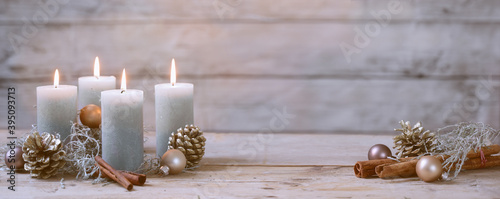 Four burning candles and Christmas decoration like cones, cinnamon and baubles against a rustic wooden background in pastel colores, copy space, panoramic format