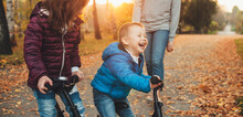 Caucasian Boy Laughing Near His Sister And Mother Riding In The Park A Bike