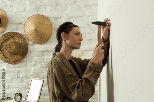 Fototapeta Young woman hammering nail into wall