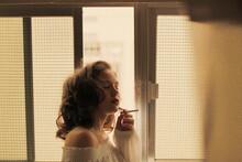 Woman Smoking Cigarette By Window