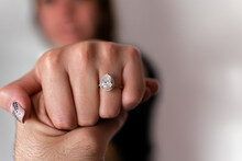 A Woman's Hand Showing Her Engagement Ring On A Blurry Background.  A Wedding Ring On Hand