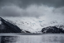 Snow Capped Mountains And Icy Lake With Lacier