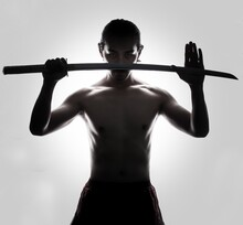 Shirtless Mid Adult Man Holding Sword While Standing Against White Background