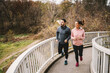 canvas print picture Full length of sporty couple running on the bridge at autumn. Healthy lifestyle concept.