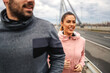 canvas print picture Smiling happy sporty couple running on the bridge at autumn at cloudy weather and preparing for marathon. Healthy lifestyle concept. Selective focus on woman.