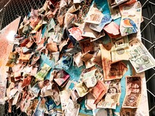 Low Angle View Of Various Paper Currencies Hanging On Fence