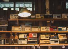 Old Radios On Shelf In Illuminated Room
