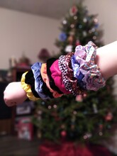 Cropped Hand Of Girl With Scrunchies Against Christmas Tree
