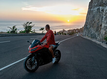 A Young Guy On A Red Sports Motorcycle Looks At Sunset. Kawasaki Ninja