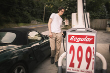 Man Refueling Car While Standing At Gas Station
