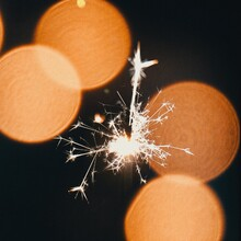 Close-up Of Illuminated Sparkler And Orange Lens Flare Against Black Background