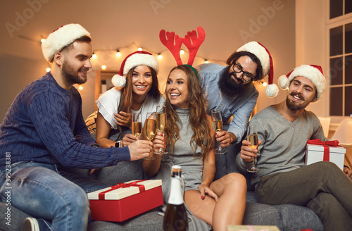 Group of smiling friends in holiday caps and accessories feasting Christmas with Wallpaper Mural