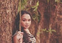 Portrait Of Teenage Girl By Tree Trunk
