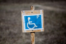Close-up Of Blue Disabled Parking Sign On Wooden Post