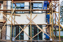 Workers Are Painting The Facade From Wooden Platform In House Is Under Construction, Remodeling, Renovation, Extension, Restoration And Reconstruction. Concept Of Home Improvement Or Renovate On The