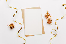 Blank Note With Envelope, Gifts And Gold Ribbon On White Background