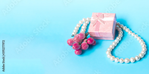 Fotografija gift box pearl necklace and a bouquet of flowers on a blue background banner, pa