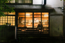 View Into Restaurant In Kyoto Japan At Night Illuminated, Dark Outside, Warm Orange Lights Inside, With One Elderly Customer, Empty Seats Around