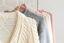 Bunch Of Knitted Warm Pastel Color Sweaters With Different Vertical Knitting Patterns Hanging On The Rack, Clearly Visible Texture. Stylish Fall / Winter Season Knitwear Clothing. Close Up, Copy Space
