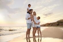 Happy Family On Sandy Beach Near Sea At Sunset