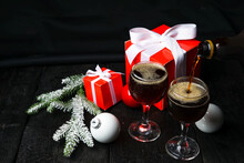 New Year's Gifts In Red Boxes With Christmas Tree Branches And Balls On A Black Background With Two Glasses Of Dark Beer Pouring Into One Drink