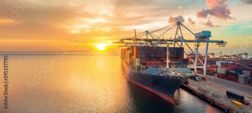 crane loading cargo container to container ship stand by in the international terminal logistic container depot sea port  concept smart freight shipping by ship at sunset