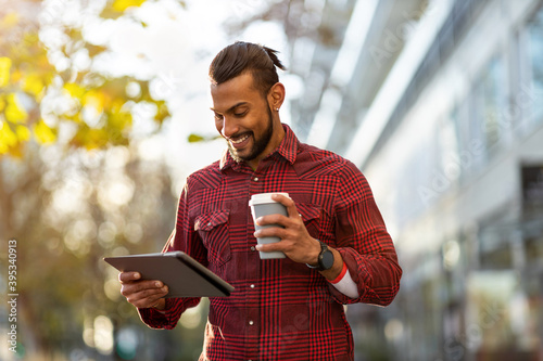 Smiling young man using tablet outdoors at urban setting Wallpaper Mural