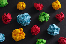 Crumpled Colorful Paper Balls On A Black Background. Idea Concept.