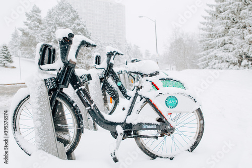Fototapeta premium Toronto, Ontario, Canada - November 22, 2020: Rent bicycles covered with fresh snow outdoor. Snow blizzard and bad weather winter condition. Heavy snowfall and snowstorm in city.