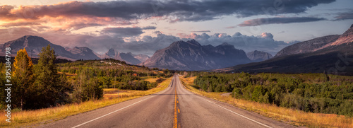 Fototapeta Beautiful View of Scenic Highway with American Rocky Mountain Landscape in the background. Colorful Summer Sunrise Sky. Taken in St Mary, Montana, United States. obraz