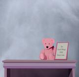 Ilustracja różowy pluszowy miś siedzący na szafce obok ramka z napisem