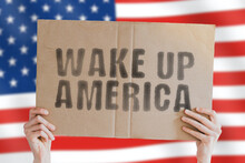 """The Phrase """" Wake Up America """" On A Banner In Men's Hand With Blurred American Flag On The Background. Government. Protest. Control. Freedom. Movement. Power"""